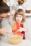 Женщина и ребенок касаясь взбитой сливк Стоковые Изображения