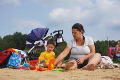 Женщина и ребенок на пляже Стоковые Изображения