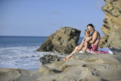 Женщина и ребенок на скалистом пляже Стоковые Изображения RF