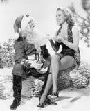 Женщина и Санта Клаус сидя совместно смеяться над (все показанные люди более длинные живущие и никакое имущество не существует Wa Стоковые Изображения