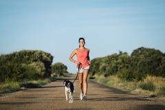 Женщина и собака бежать на проселочной дороге Стоковая Фотография RF