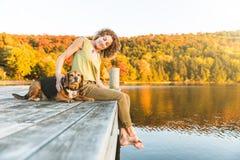Женщина и собака ослабляя на доке Стоковые Изображения RF