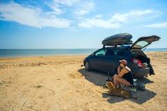 Женщина и собака сидя около автомобиля Стоковое Фото
