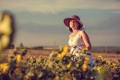 Женщина и солнцецветы стоковое изображение