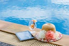 Женщина и таблетка шляпы около бассейна Стоковое Изображение RF