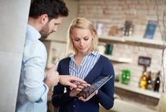 Женщина и человек используя таблетку совместно стоковые изображения rf