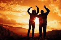 Женщина и человек на заходе солнца Стоковые Изображения RF
