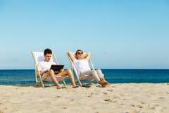 Женщина и человек ослабляя на пляже Стоковые Изображения RF