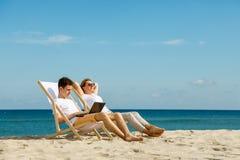Женщина и человек ослабляя на пляже Стоковая Фотография RF