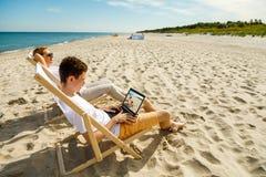 Женщина и человек ослабляя на пляже Стоковые Изображения