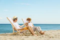 Женщина и человек ослабляя на пляже Стоковое фото RF