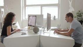 Женщина и человек работая на компьютере сидя в деловом центре внутри помещения
