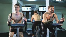 Женщина и человек фитнеса счастливые на неподвижном велосипеде делая закручивать на спортзал Подходящая молодая женщина разрабаты акции видеоматериалы
