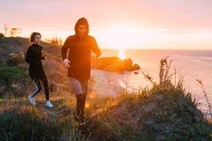 Женщина и человек бежать на пляже Стоковые Изображения