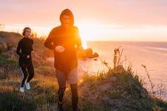 Женщина и человек бежать на пляже Стоковое Изображение