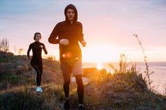 Женщина и человек бежать на пляже Стоковые Фотографии RF