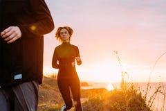 Женщина и человек бежать на пляже Стоковые Изображения RF