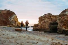Женщина и человек бежать на пляже Стоковое Фото