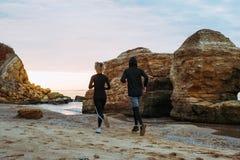 Женщина и человек бежать на пляже Стоковое Изображение RF