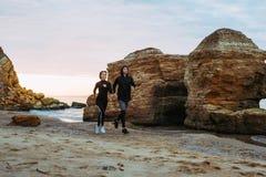 Женщина и человек бежать на пляже Стоковое фото RF