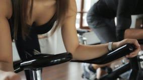 Женщина и человек включили на неподвижном велосипеде в стоящем методе видеоматериал