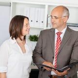 Женщина и человек говоря в офисе Стоковые Фото