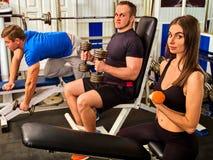 Женщина и человек держа разминку гантели на спортзале Люди друзей Стоковое Изображение