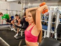 Женщина и человек держа разминку гантели на спортзале Стоковые Фотографии RF