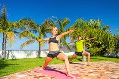 Женщина и человек делая йогу outdoors Стоковое фото RF