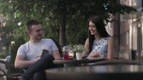 Женщина и человек имеют переговор в кафе лета акции видеоматериалы