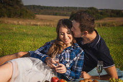 Женщина и человек имея пикник в поле запахните ее волосами Стоковые Фото