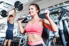 Женщина и человек имея тренировку спорта в спортзале фитнеса Стоковое фото RF