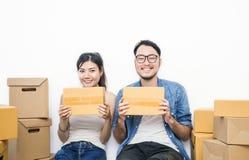Женщина и человек который их руки держа коробку работая дома концепция, онлайн упаковка маркетинга и поставка Стоковые Фото