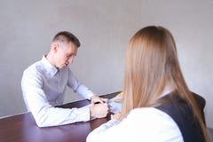 Женщина и человек обсуждают работу Они сидя в офисе деревянных животиков Стоковая Фотография