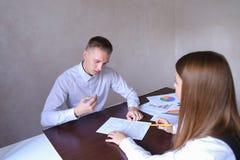 Женщина и человек обсуждают работу Они сидя в офисе деревянных животиков Стоковое фото RF