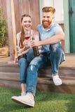 Женщина и человек отдыхая с пивом и вином на крылечке Стоковое Изображение RF
