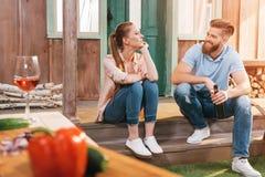 Женщина и человек отдыхая с пивом и вином на крылечке Стоковое Изображение