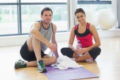 Женщина и человек при бутылки с водой сидя на спортзале Стоковая Фотография RF