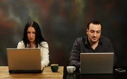 Женщина и человек работая на компьтер-книжки Стоковые Изображения