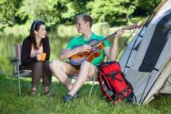 Женщина и человек располагаясь лагерем над озером Стоковое фото RF