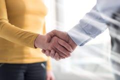 Женщина и человек тряся руки в офисе, влияние световых лучей Стоковое фото RF