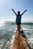 Женщина идя вне на стену пролома с волнами океана в фронте стоковое фото rf