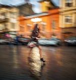 Женщина идя вниз с улицы после дождя Стоковые Фотографии RF