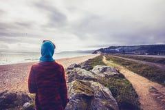 Женщина идя вдоль прибрежного пути на пляже в зиме Стоковая Фотография RF