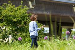 Женщина идя в парк города смотря ее мобильный телефон Стоковая Фотография