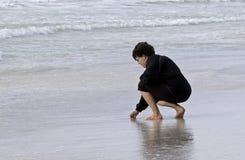 Женщина идя в прибой ища раковины моря Стоковая Фотография RF