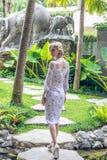 Женщина идя в тропический сад острова Бали, Индонезии стоковые фотографии rf