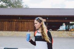 женщина идя в улицу и держа чашку питья Стоковое Фото