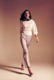 Женщина идя в striped брюки и верхнюю часть в студии стоковое фото rf