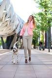 Женщина идя ее собака и говоря на мобильном телефоне в городе Стоковые Фотографии RF